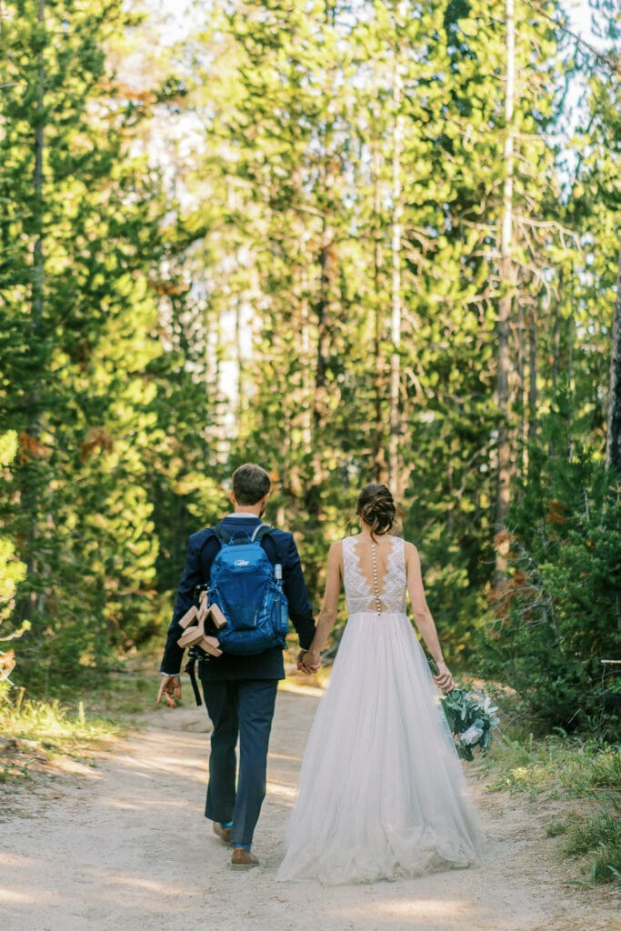 Bride and groom hiking down a dusty trail in a forest in Wyoming.