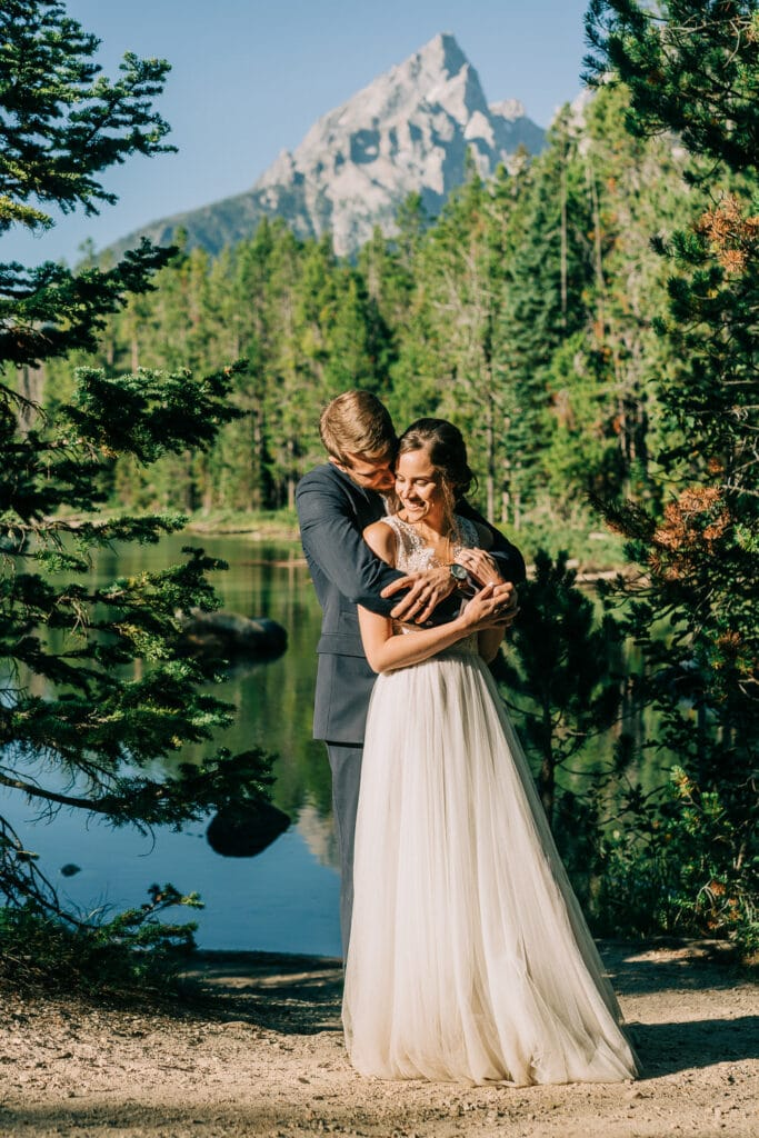 Bride and groom hug in front of the Grand Teton mountains during their elopement in summer.