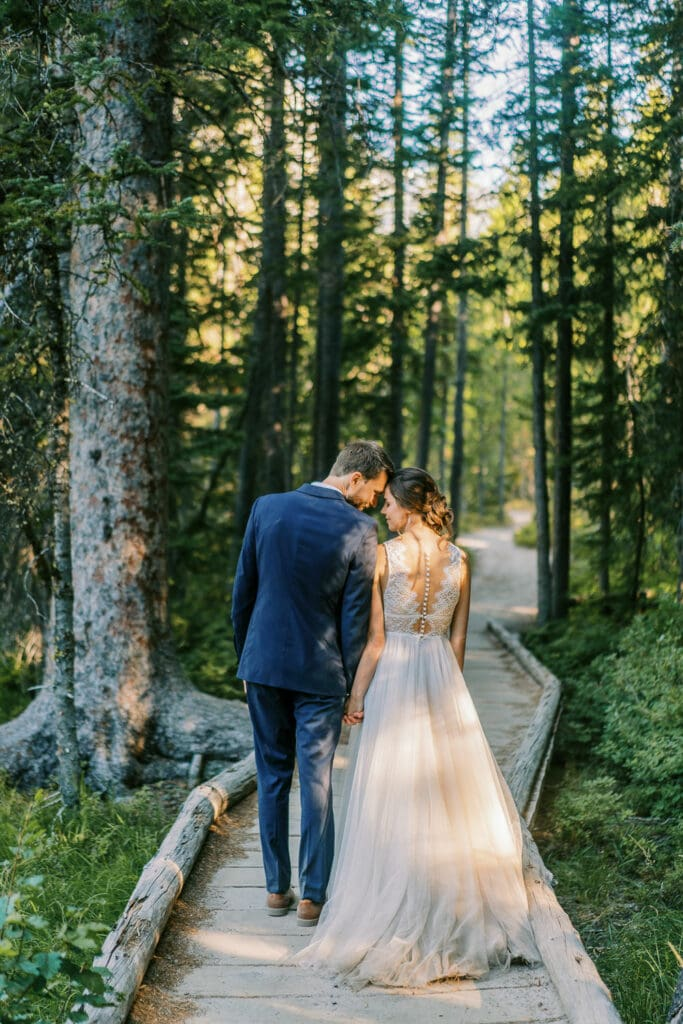 Bride and groom hiking on a boardwalk in Grand Teton National Park after sunrise.