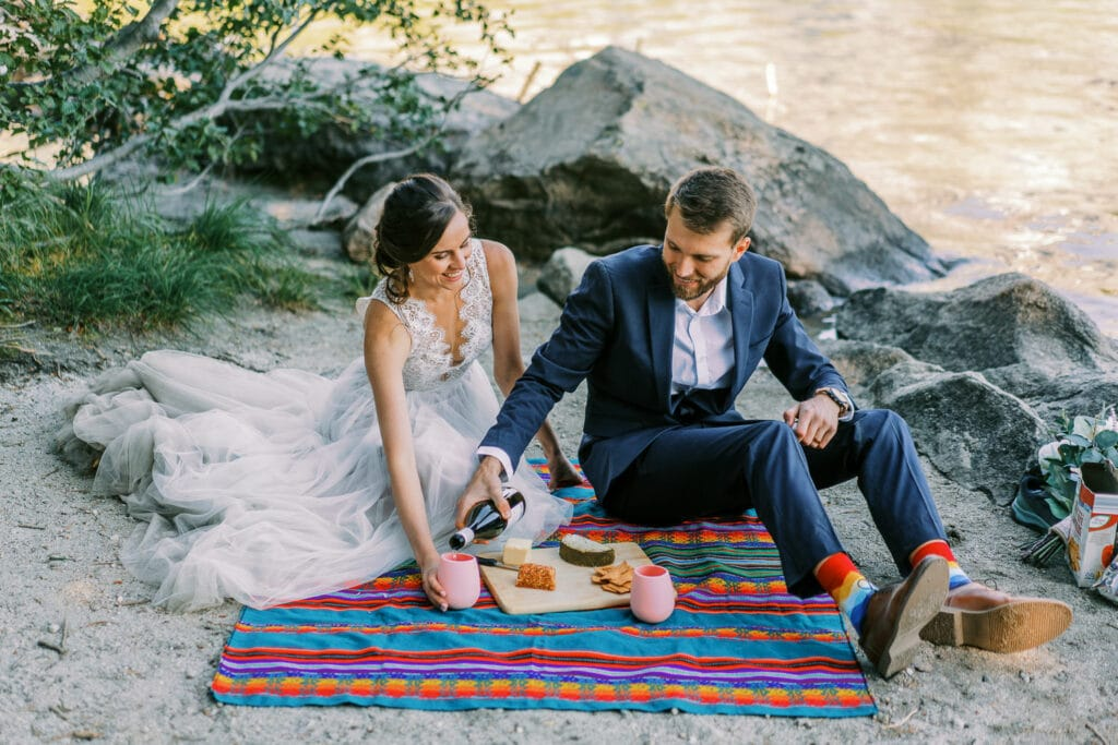 Bride and groom have a picnic in Grand Teton National Forest by a lake.