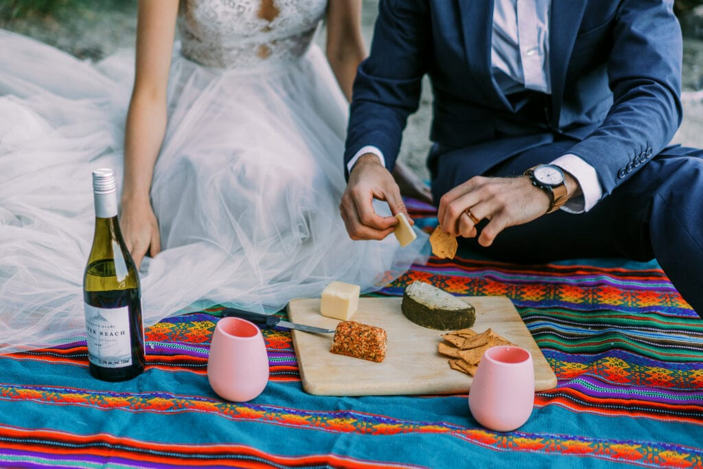 Bride and groom have a picnic with wine, cheese, and crackers at their elopement in Wyoming.