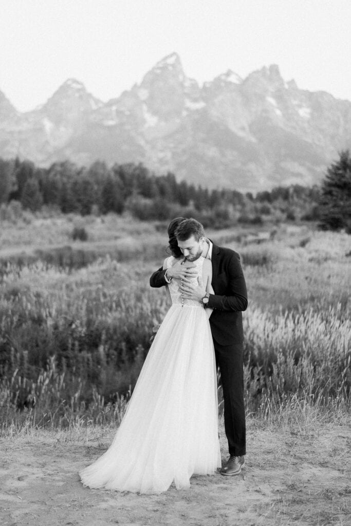Romantic black and white photo of a bride and groom hugging at an elopement in the Grand Tetons.
