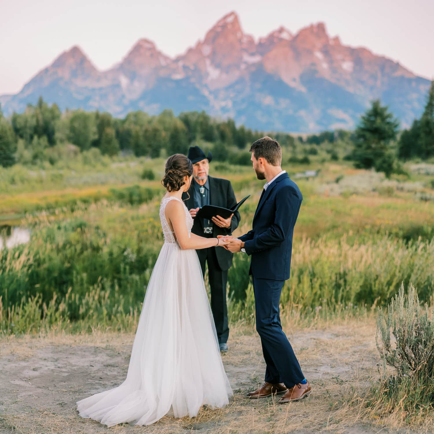 Bride and groom look at officiant during their wedding ceremony in the Tetons.