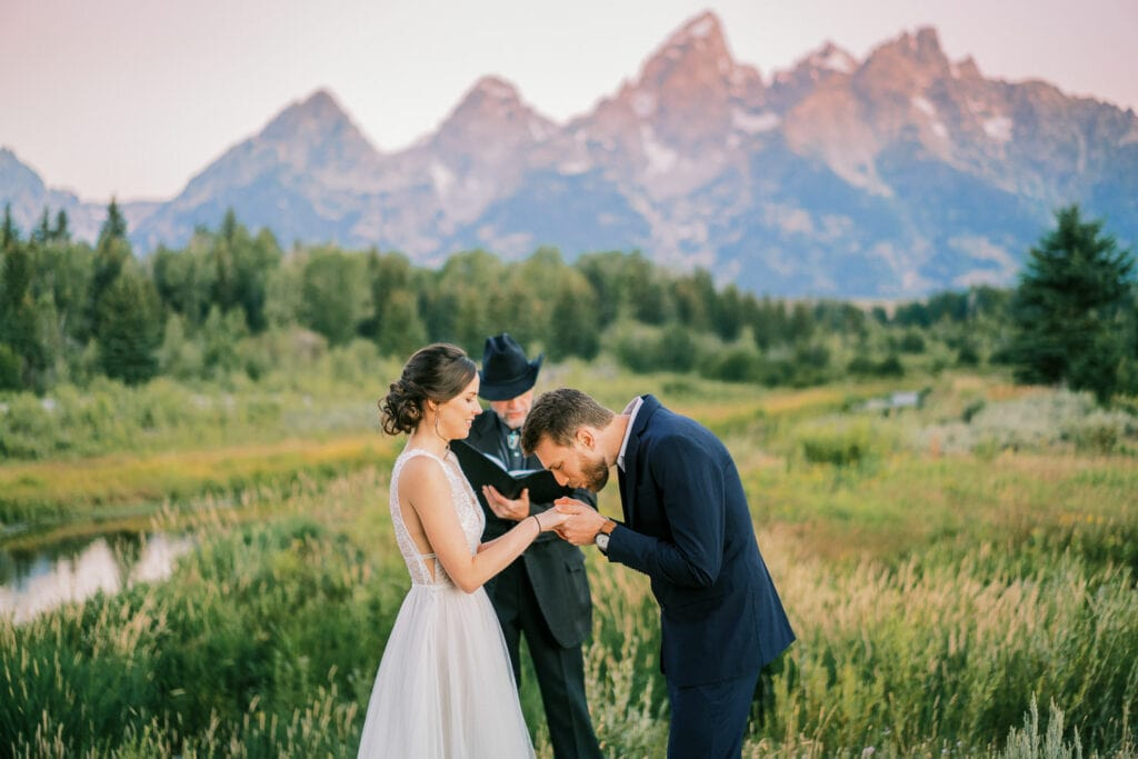 Groom warms the hands of his bride during a cold sunrise ceremony in the Grand Tetons.