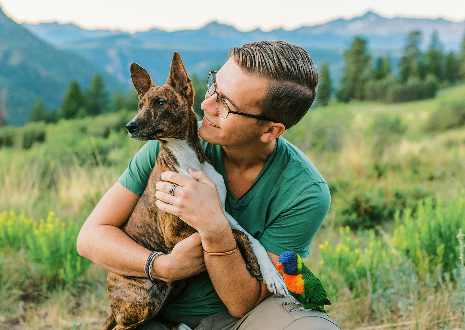 Malachi Lewis at Shell Creek Photography with a dog and parrot.