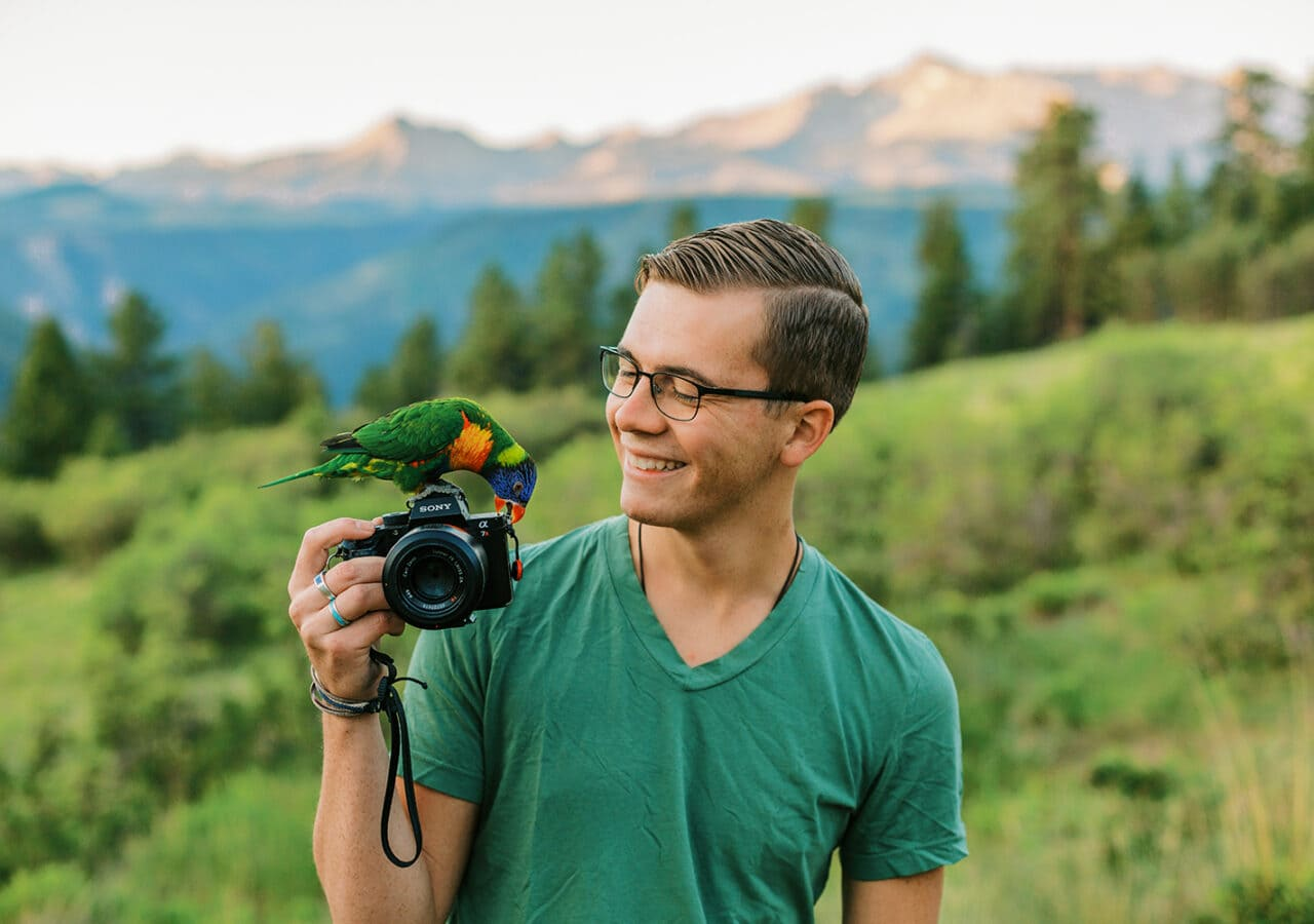 Malachi Lewis of Shell Creek Photography with a parrot on a camera.
