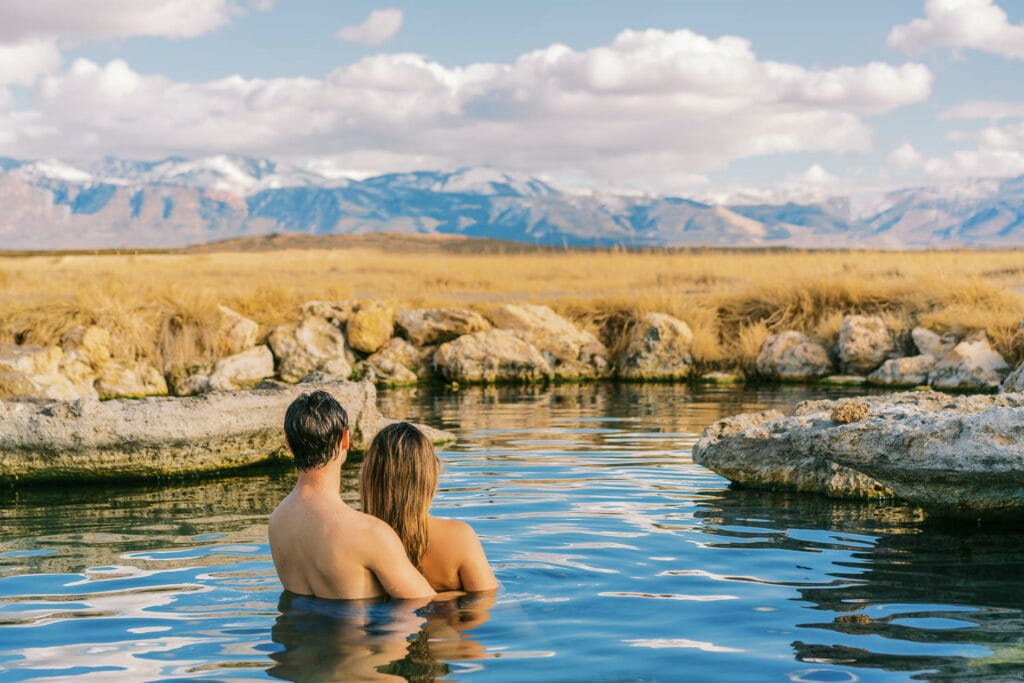A couple relaxes in a Utah hot springs after their elopement in the mountains.