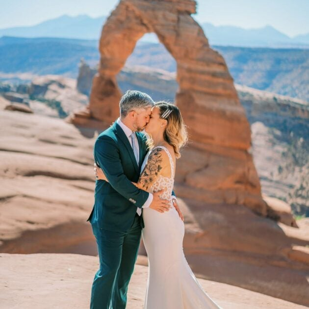 Bride and groom kiss in front of Delicate Arch during their hiking elopement.