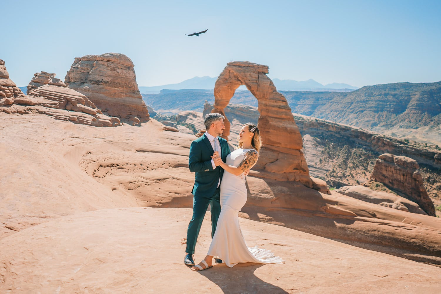 Moab elopement photographer with a bride and groom in Arches National Park near Delicate Arch in summer.