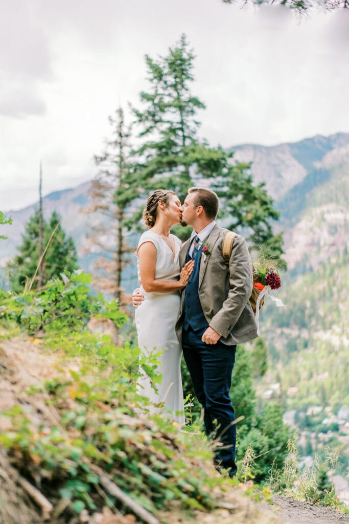Bride and groom kissing with a view of the mountains in the background.