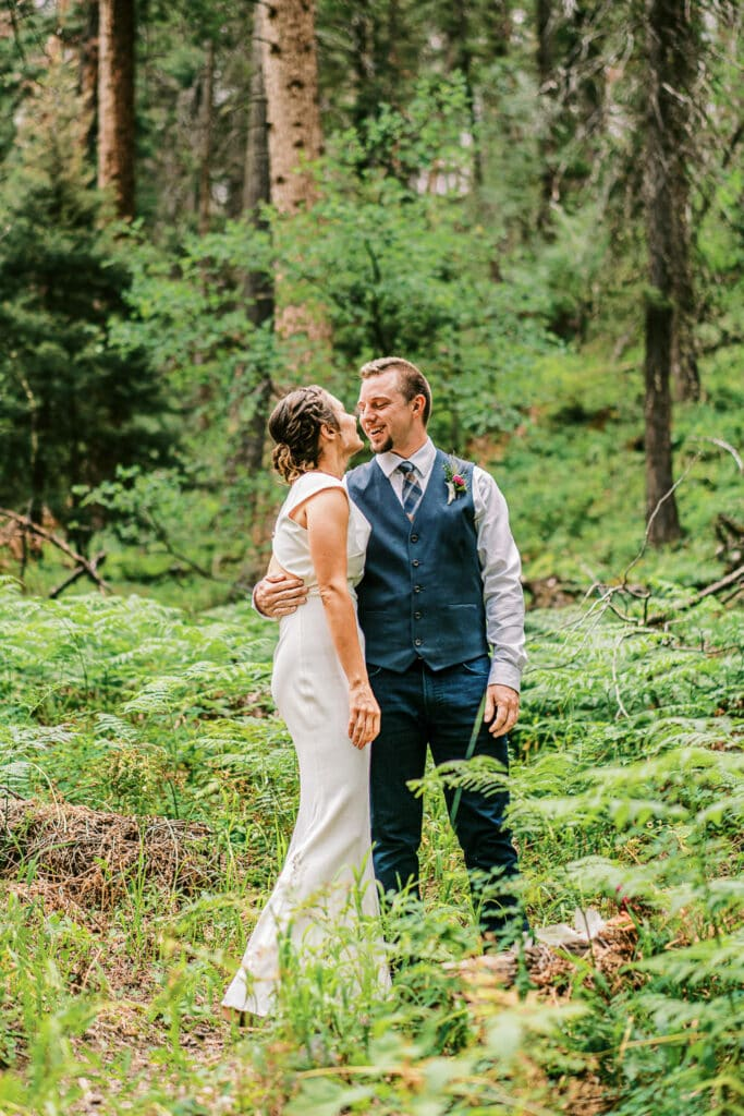 Bride and groom stand in a forest surrounded by ferns.