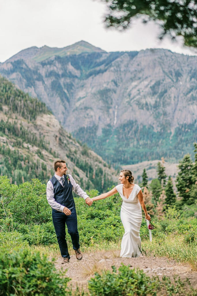 Bride and groom having fun hiking for their wedding day in the mountains of Colorado.