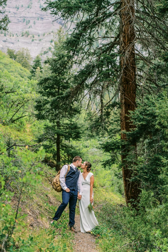 Bride and groom hiking in a suit and a wedding dress in the mountains.