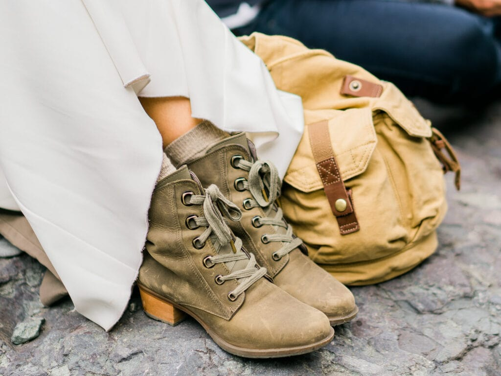 Bride's hiking boots with a wedding dress and a backpack.