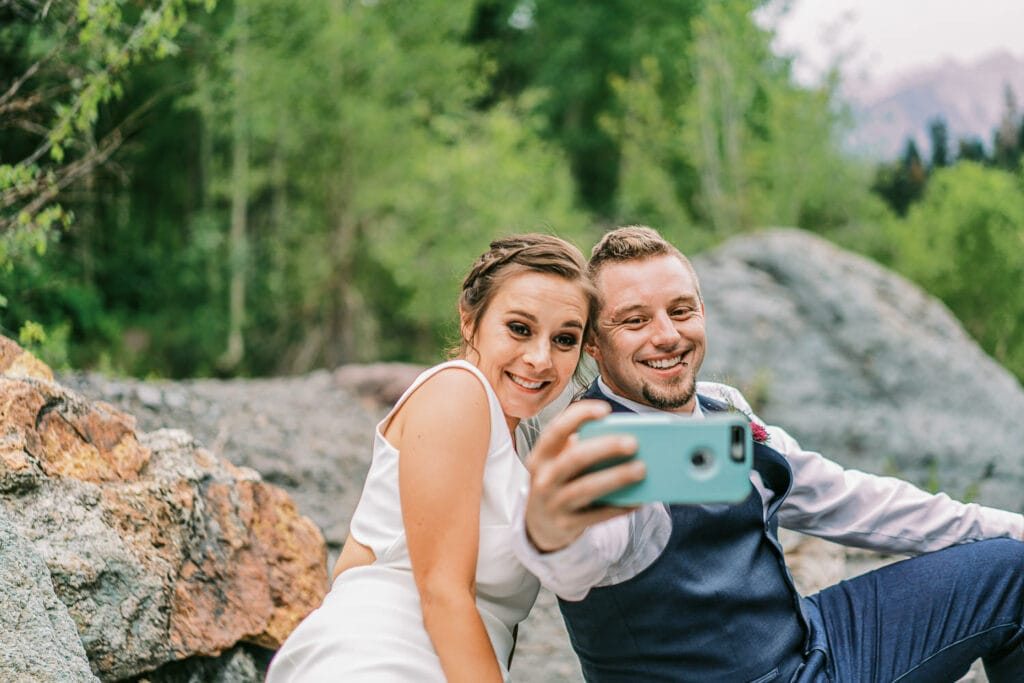 Bride and groom take a selfie at their adventure wedding in Ouray, Colorado.