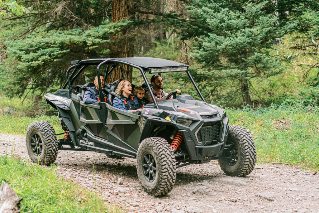 Guests at a wedding in Ouray, Colorado arrive in an ATV vehicle in the mountains.