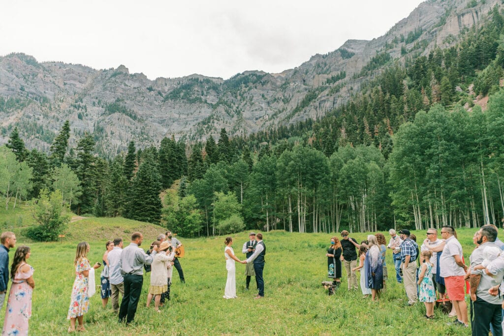 Bride and groom say their vows outdoors in the mountains of Ouray, Colorado while surrounded by guests.
