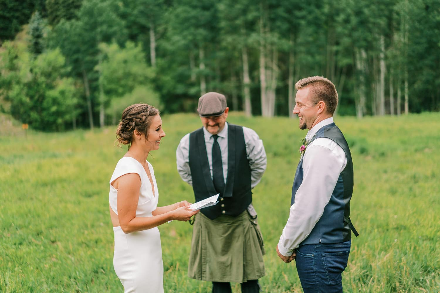 Bride says vows to her groom at an outdoor wedding in Colorado.