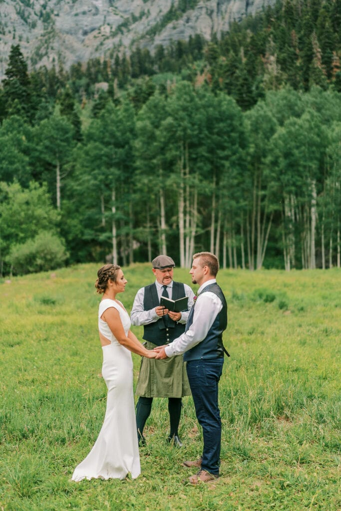 Bride and groom say their vows with an officiant in a kilt in the mountains of Colorado.