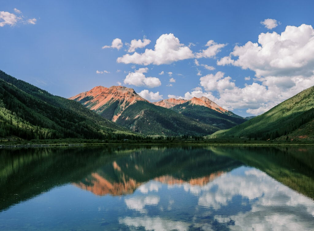 Puffy clouds and a blue sky reflect in an alpine lake near Ouray, Colorado with views of Red Mountain on a summer day.
