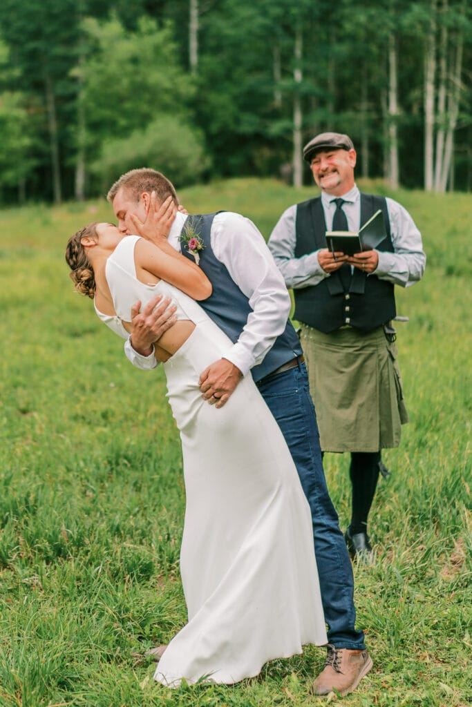 Bride and groom's first kiss during an outdoor wedding in Colorado.