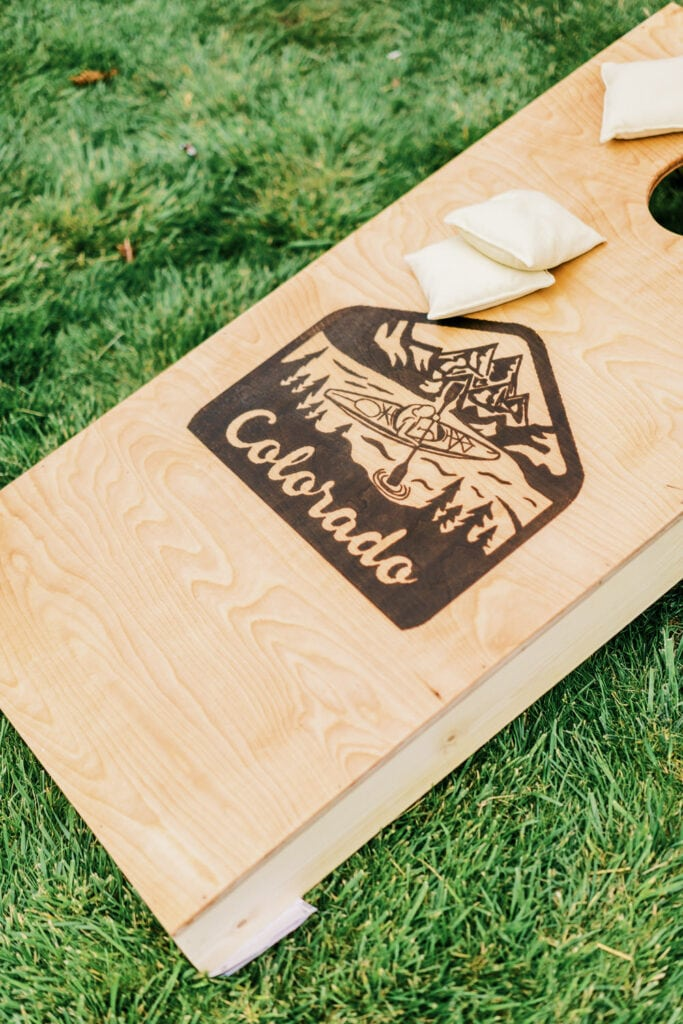 A corn hole board with bean bags and a Colorado logo on the board.