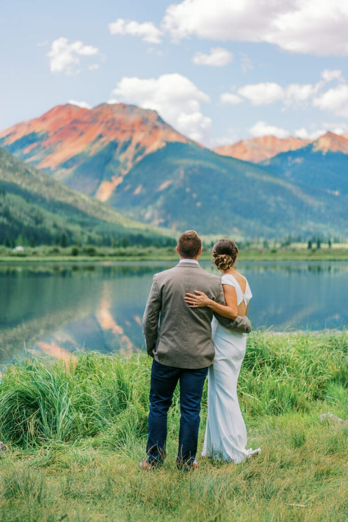 Bride and groom have first look above Ouray, Colorado at an alpine lake with views of the Red Mountains of the San Juan Mountains.
