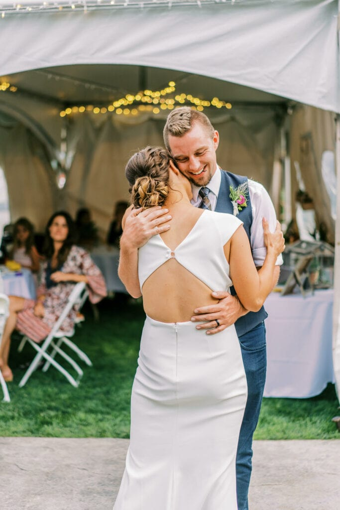 Bride and groom hug during their first dance at their Colorado wedding.