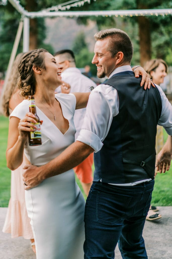 Groom dances with bride as they are both smiling with drinks in their hand.