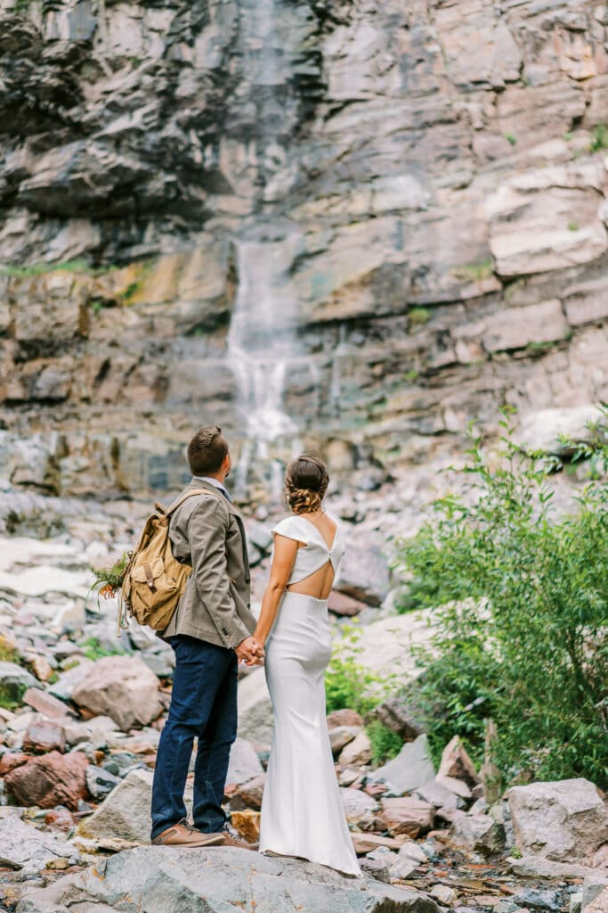 Bride and groom stop for a moment to look at Cascade Falls in Ouray, Colorado during their adventure wedding.