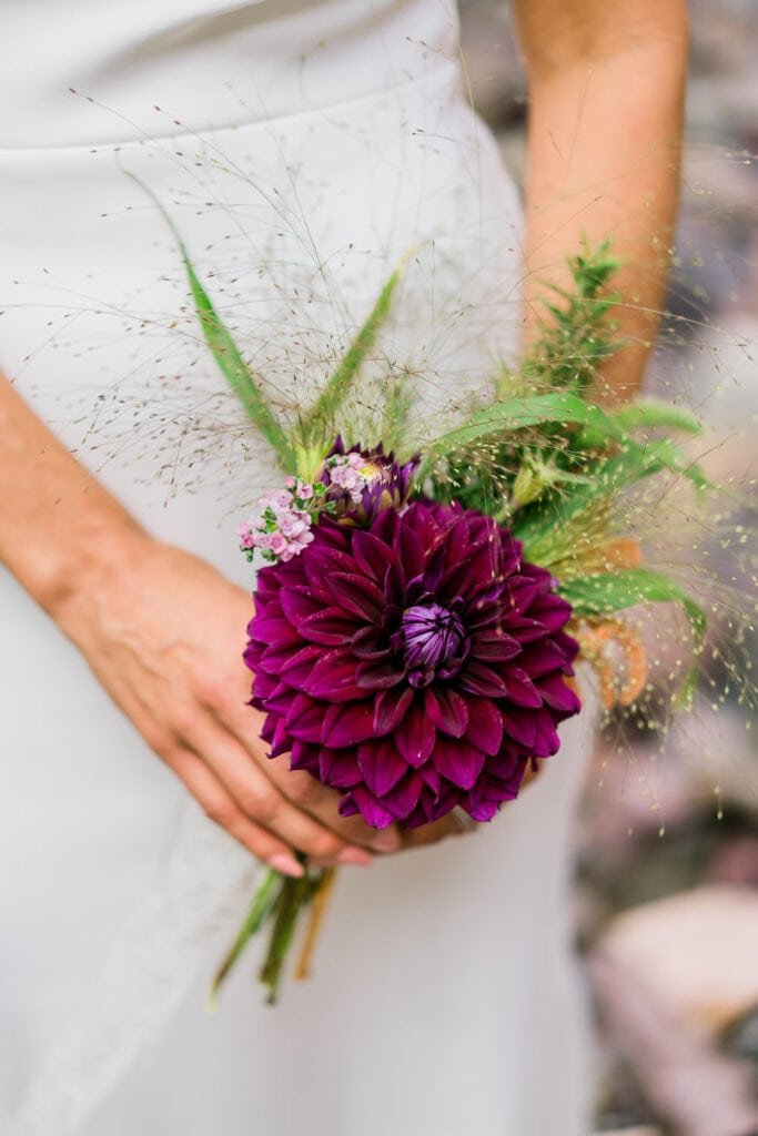 Bride holds a small purple wedding bouquet made with a large dahlia flower.