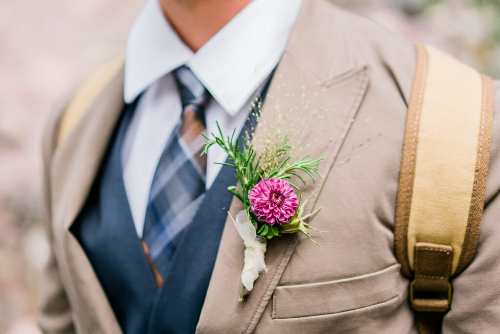 Groom's boutonnière made with a pink flower and some rosemary and a thistle for greenery.