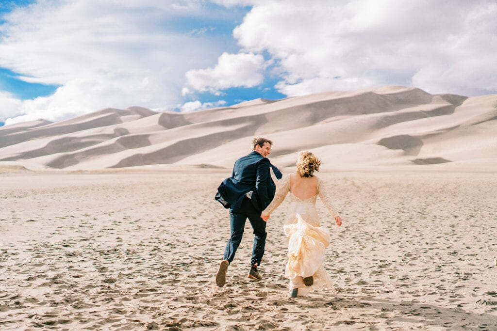 Bride and groom running in the sand in Great Sand Dunes National Park in Colorado.