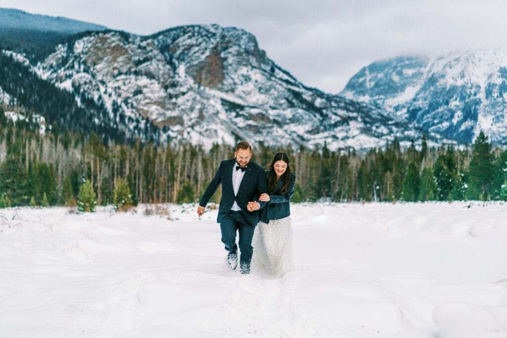Bride and groom walk together in the snow during their elopement in Grand Lake, Colorado near Rocky Mountain National Park in winter.