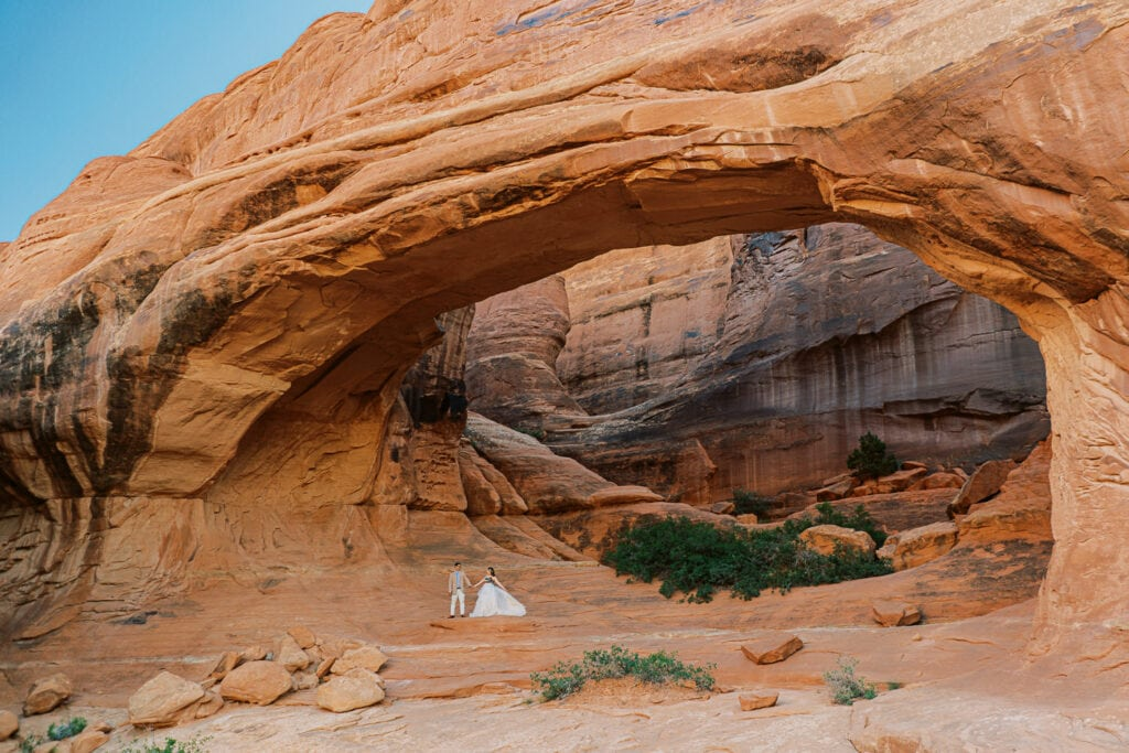 Bride and groom stand under a red stone arch during their Moab elopement in Arches National Park.