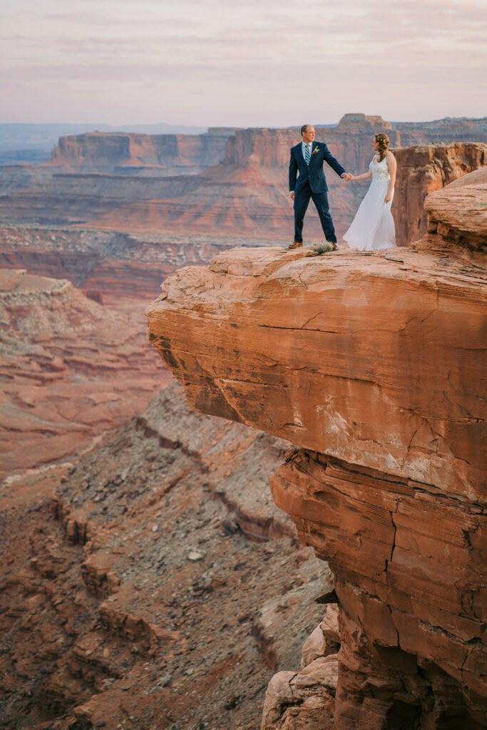 A bride and groom hold hands on the edge of a cliff during their elopement in Moab, Utah.